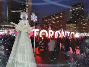 Stiltwalker Toronto sign at night Holiday Fair in the Square 2017 Nathan Phillips Hala on Stilts Entertainment