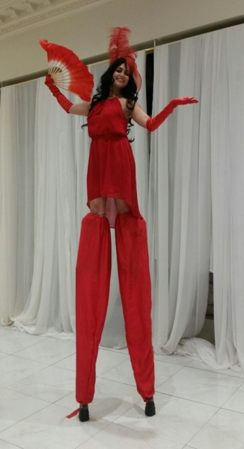 Hala on stilts stunning in red stiltwalker GTA Toronto