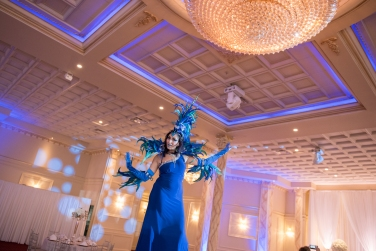 Hala on stilts entertainment blue carnival feathers costume circus stilt-walker Photo by Summerhill weddings